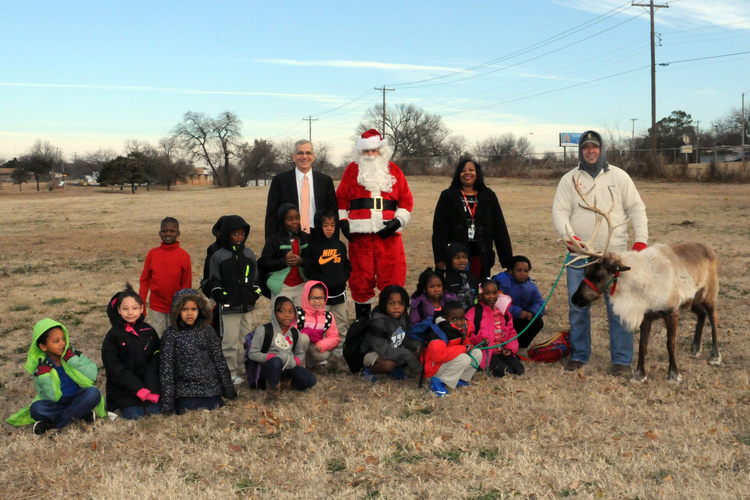 Secretary of Agriculture Jim Reese poses with Santa and students from F. D. Moon Academy in Oklahoma City during a visit with Prancer the reindeer.